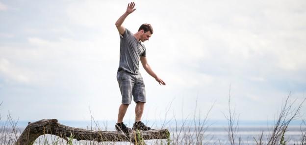 man balances on log